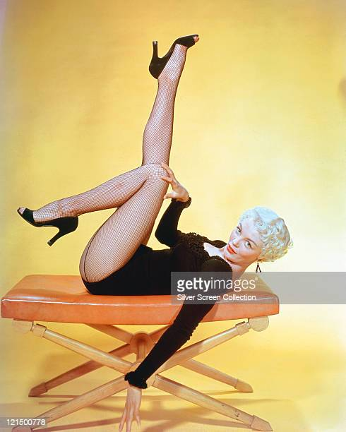 Sheree North US actress singer and dancer wearing a black longsleeved leotard with fishnet stockings laying on her back on a stool with her legs in...