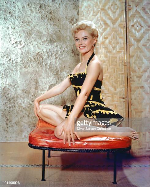 Sheree North US actress singer and dancer wearing a blackandyellow minidress posing on a lowlevel stool with a red cushion in a studio portrait circa...