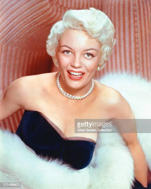 Sheree North US actress singer and dancer wearing a strapless black top and a pearl necklace and wrapped in white fur smiling in a studio portrait...