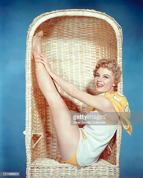 Sheree North US actress singer and dancer wearing a yellowandwhite playsuit sitting in a wicker chair smiling in a studio portrait against a blue...