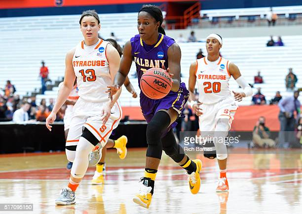 Shereesha Richards of the Albany Great Danes dribbles the ball up the court against the defense of Brianna Butler of the Syracuse Orange during the...