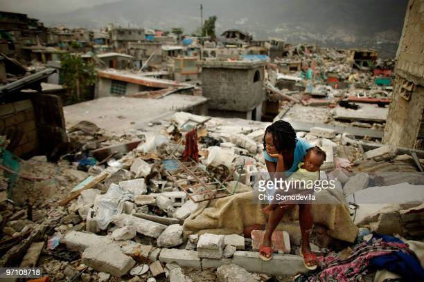 Sherider Anilus and her daughter, 9-month-old Monica, sit on the spot where her home collapsed during last month's 7.0 earthquake in the Fort...
