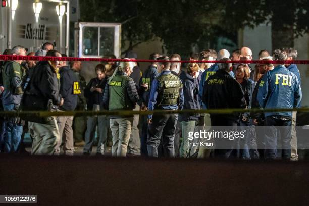Sheriff and FBI investigators huddled at the command post after a gunman opened fire late Wednesday at a Thousand Oaks bar packed with hundreds of...