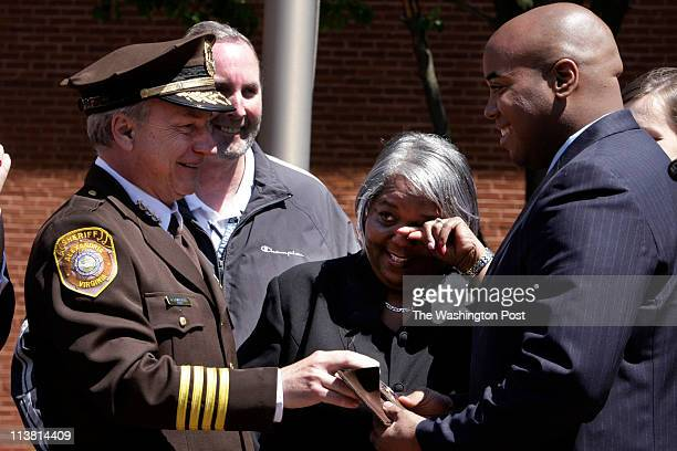Sheriff Dana Lawhorne gives Kevin Truesdale his deputy sheriff badge as his mother Zita Truesdale Noyes at center wipes away at tear after Kevin's...