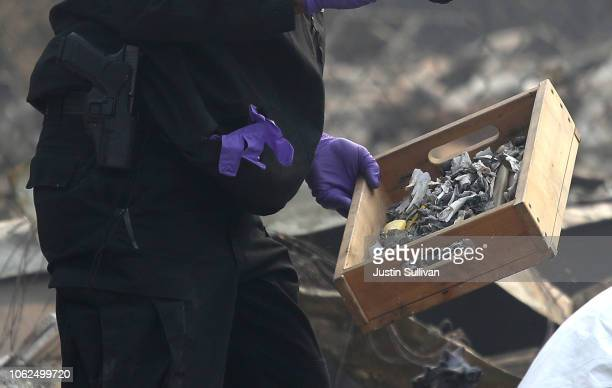 A sheriff deputy holds a box of bone fragments that were found at a home destroyed by the Camp Fire on November 16 2018 in Paradise California Fueled...