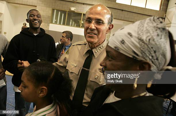 Sheriff Lee Baca shares a few laughs with James Simpsonleft and Teresa Davis and daughter Archa after a town hall meeting in Rancho Dominguez...