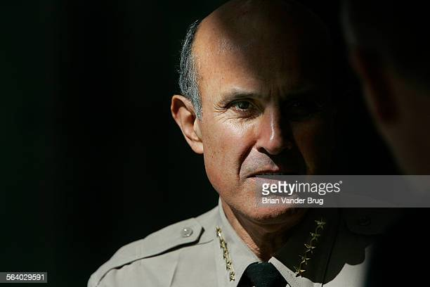 Sheriff Lee Baca waits in the shadows for a press conference to begin following a roundtable meeting on airport and port security with Congresswoman...
