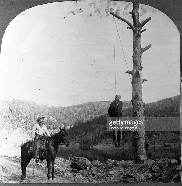 A sheriff on horseback finds a stagecoach robber apparently executed by one of his victims hanging by the neck from a tree Boulder Colorado