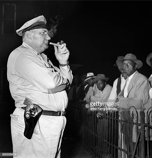 Sheriff stands smoking a pipe in front of a crowd at a voting registration site in 1946 in Mississippi.