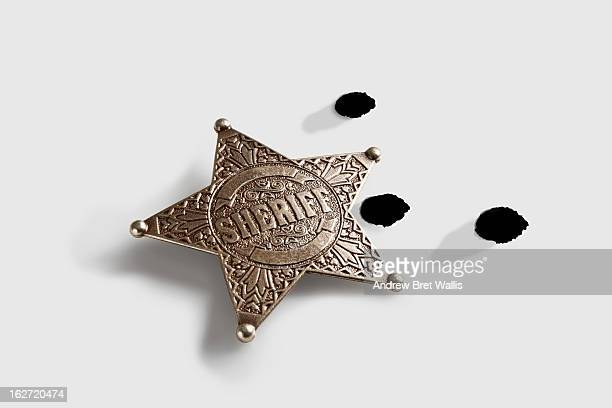 Sheriff's badge and bullet holes