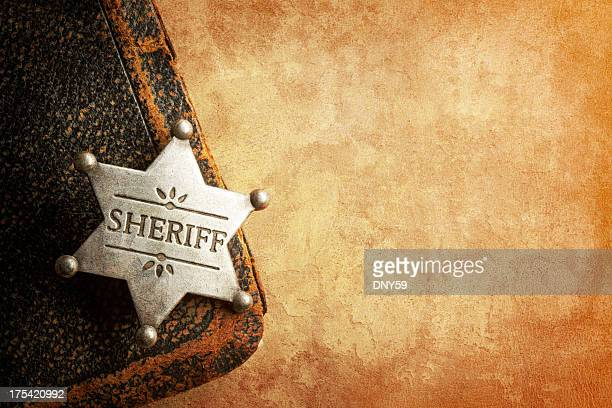 sheriff's badge on warm textured surface - sheriff stock pictures, royalty-free photos & images