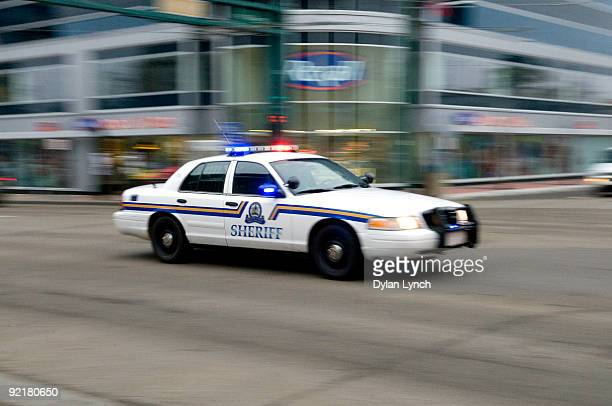 A sheriff's car speeds through the downtown streets on its way to a hostage situation at the Workers' Compensation Board building on October 21 2009...