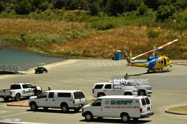 Sheriff's department vehicles and a helicopter sit in a parking lot along with emergency workers at Lake Piru, where actress Naya Rivera was reported...
