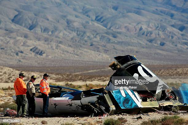 Sheriff's deputies inspect the wreckage of the Virgin Galactic SpaceShip 2 in a desert field November 2 2014 north of Mojave California on The Virgin...