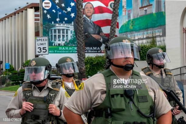 Sheriff's deputies stand guard near a mural of President Barack Obama as activists and relatives of Andres Guardado, who was shot and killed by a...