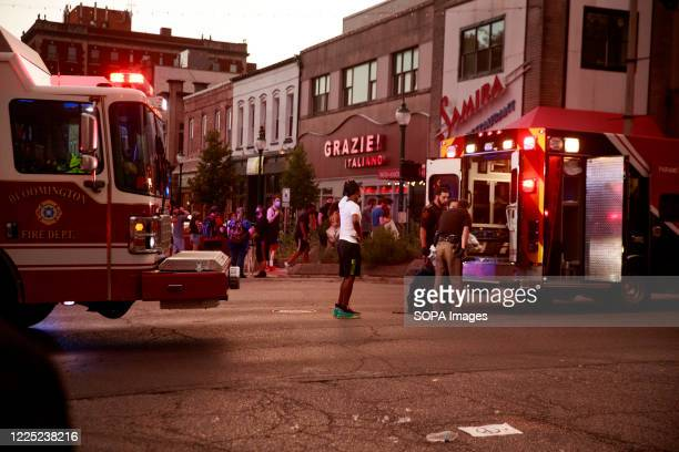 Sheriff's deputies stand outside an ambulance after a red car that hit two protesters and carried them several blocks at a high rate of speed before...