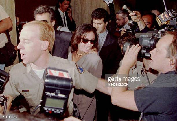 A sheriff's deputy clears the way through a crowd for Heidi Fleiss the alleged Madam to the Stars as she arrives at the Criminal Courts building for...