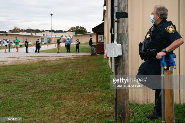 Sheriff's deputy looks out at the line to vote at an early voting location at the Gwinnett County Fairgrounds on October 24 in Lawrenceville,...