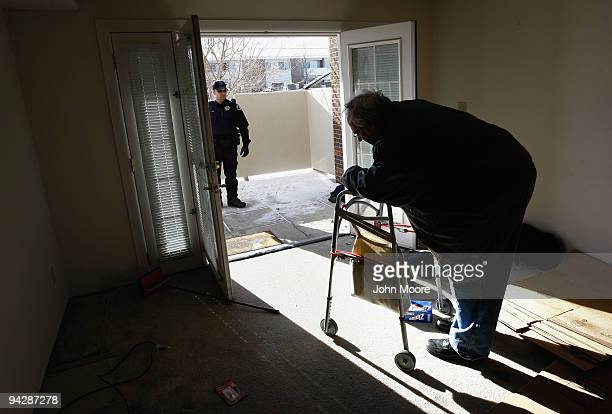 Sheriff's deputy Seth Poe waits to escort Harvey Lesser from his apartment after serving him with a court order for eviction on December 11, 2009 in...