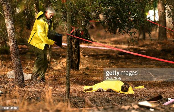 A sheriffs deputy stands near a dead body near Hot Springs Road in Montecito after a major storm hit the burn area Tuesday January 9 2018 in...
