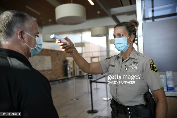 Sheriff's deputy takes an employee's temperature as at Las Colinas women's Detention Facility in Santee, California on Wednesday, April22, 2020....
