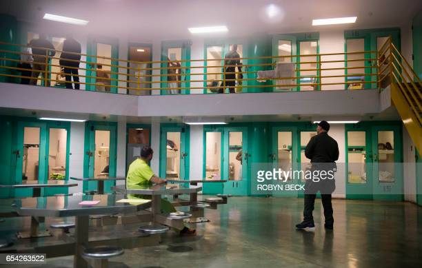 TOPSHOT A sheriff's deputy talks to an immigration detainee in a high security housing unit at the Theo Lacy Facility a county jail which also houses...