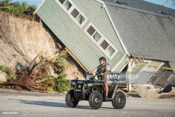 A sheriff's officer passes by a beachfront home destroyed by Hurricane Irma on September 13 2017 in Vilano Beach Florida Nearly 4 million people...