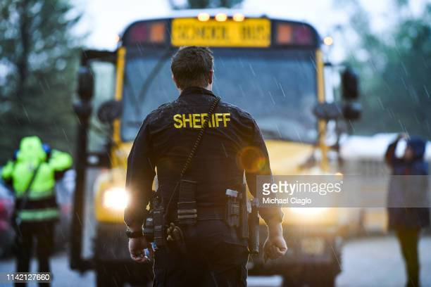 A sheriff's officer watches as students get off buses after being evacuated to the Recreation Center at Northridge after at least seven students were...