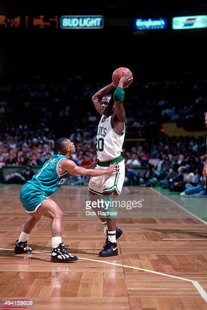 Sherman Douglas of the Boston Celtics looks to pass against Muggsy Bogues of the Charlotte Hornets during a game played at the Boston Garden in...