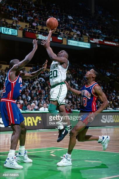 Sherman Douglas of the Boston Celtics shoots against Olden Polynice and Dennis Rodman of the Detroit Pistons during a game played at the Boston...