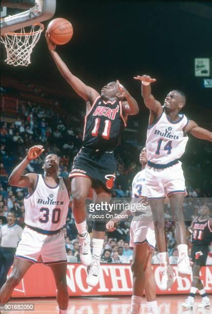 Sherman Douglas of the Miami Heat goes in for a layup over Bernard King and AJ English of the Washington Bullets during an NBA basketball game circa...