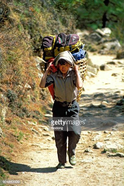 Sherpa carrying bags on a trekking path Nepal