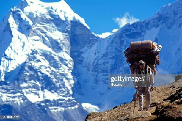 Sherpa carrying bags on an Everest trail Nepal