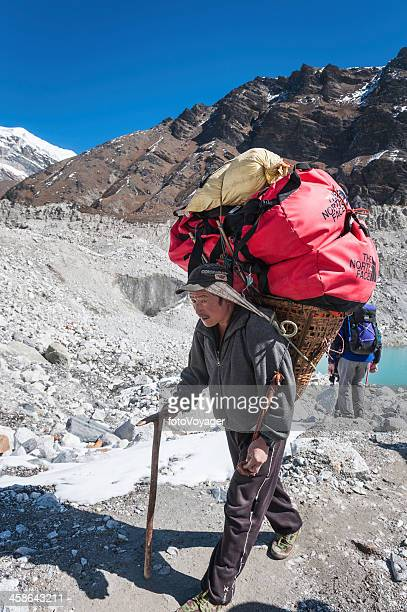 Sherpa carrying expedition kit on glacier Himalayas
