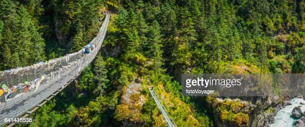 Sherpa crossing highwire rope bridge over mountain canyon Himalayas Nepal