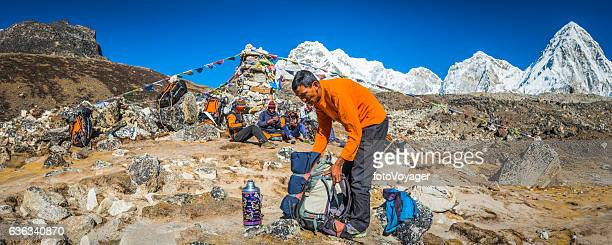 Sherpa guide and porters beside prayer flags Himalaya mountains Nepal