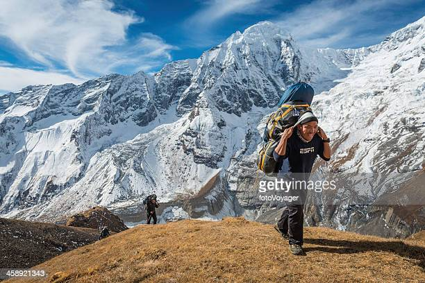 Sherpa guide carrying expedition kit Himalayas Nepal