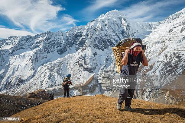 Sherpa mountaineers carrying heavy expedition loads high in Himalayas Nepal