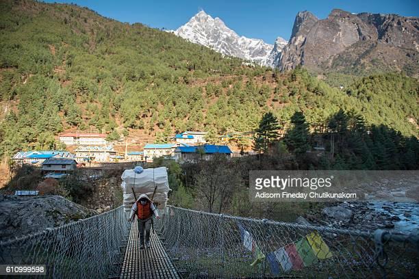 Sherpa Porter carrying a heavy Load cross the bridge