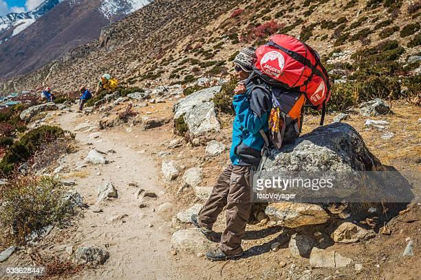 Sherpa porter carrying expedition kit on Himalaya mountain trail Nepal