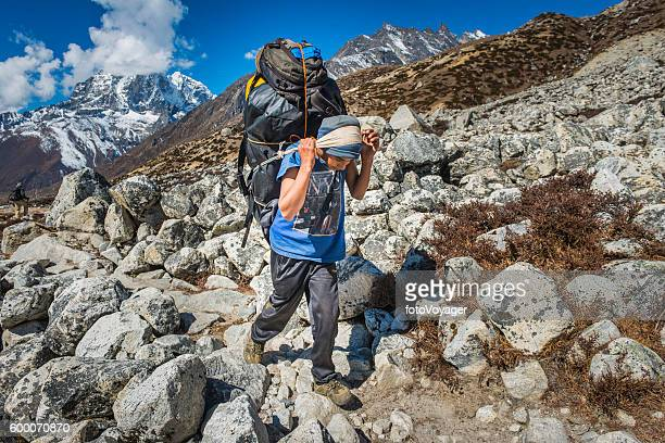 Sherpa porter carrying expedition kitbags along Everest trail Himalayas Nepal