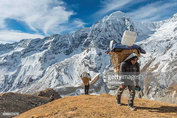 Sherpa porter carrying expedition load high in Himalaya mountains Nepal