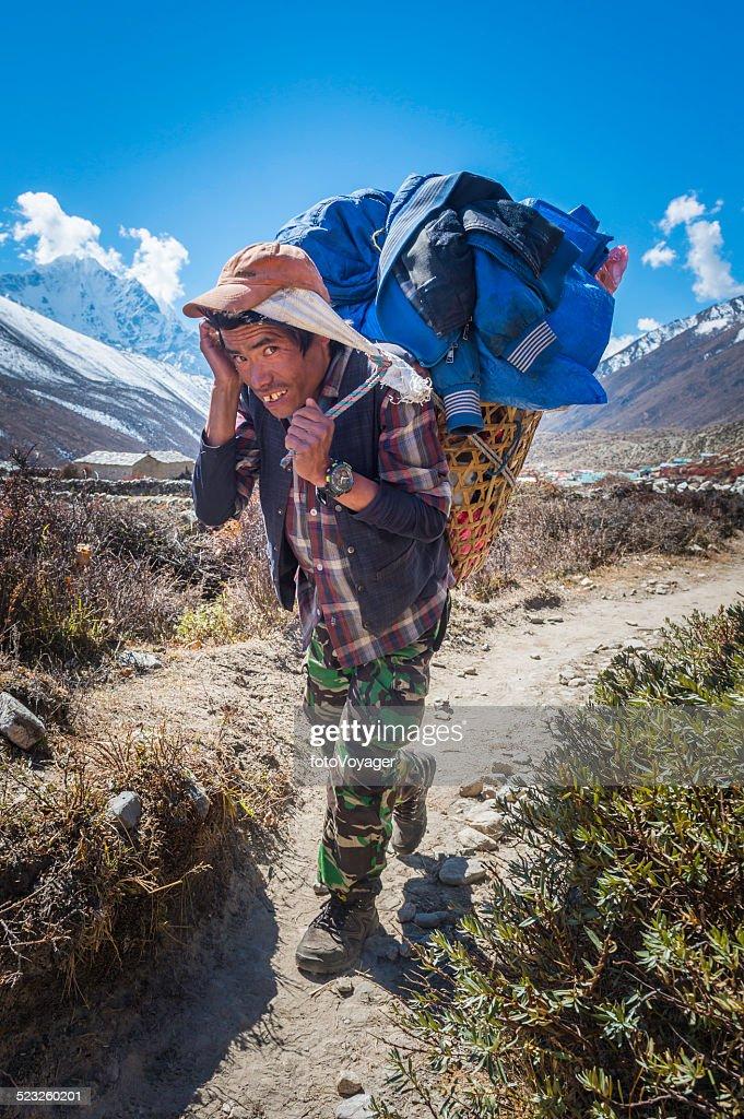 Sherpa porter carrying heavy basket along trail Himalayas Nepal : Stock Photo