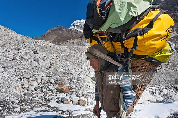 Sherpa porter carrying heavy expedition load across glacier Himalayas Nepal