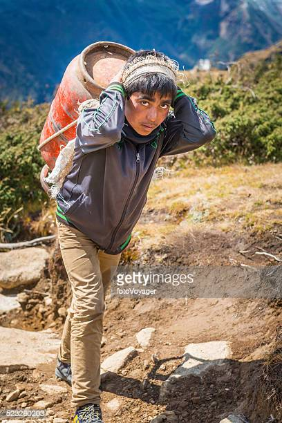 Sherpa porter carrying heavy gas bottle along Himalaya mountain trail