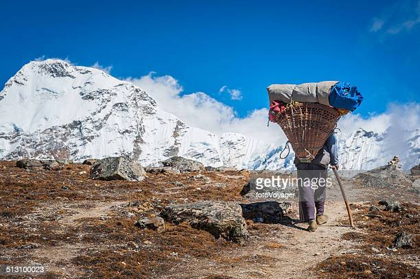 Sherpa porter carrying heavy load in traditional basket Himalayas Nepal