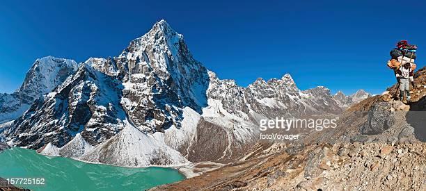 Sherpa porter carrying heavy load on Himalaya mountain trail Nepal