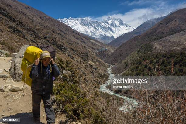 Sherpa Porter with Everest, Nuptse and Lhotse mountain peak in the background