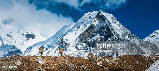 sherpa porters carrying baskets towards island peak himalaya mountains nepal - himalaya stockfoto's en -beelden