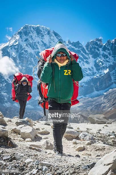 ンゴズンパ氷河ヒマラヤネパール上空に遠征キットを運ぶシェルパポーター - 職業 ポーター ストックフォトと画像